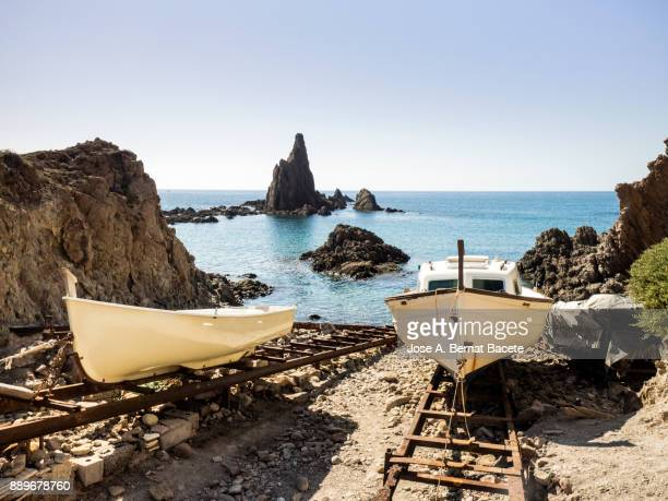 Small boats of traditional fishing aground in the sand in a small cove between rocks.. Cabo de Gata - Nijar Natural Park, Sirens reef, Beach, Biosphere Reserve, Almeria, Andalusia, Spain
