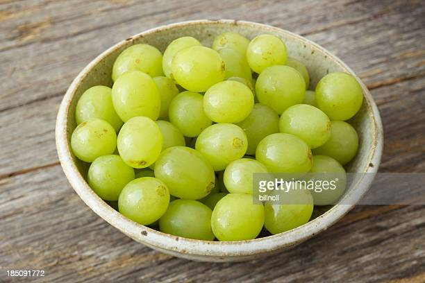 Small bowl of organic green grapes on rustic wood