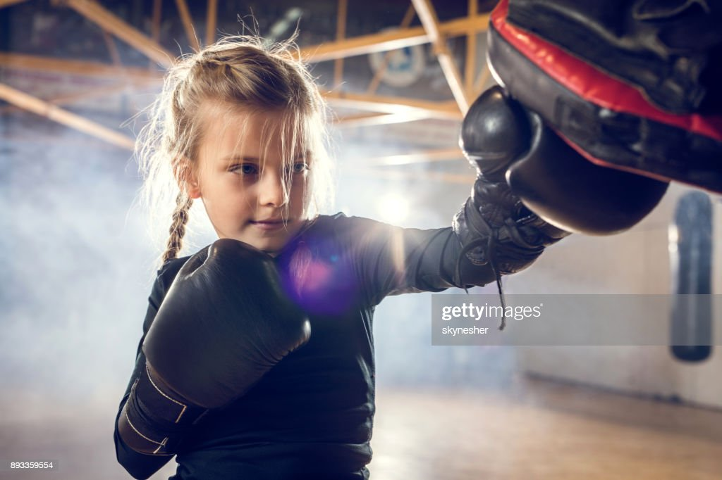 Small boxer exercising punches on a sports training in a gym. : Stock Photo