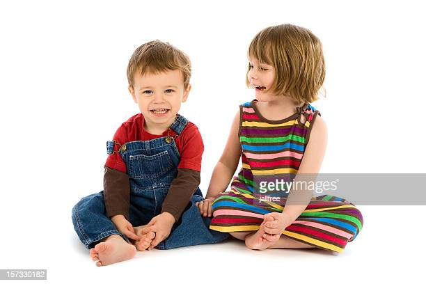 Small boy and girl sitting together smiling on white