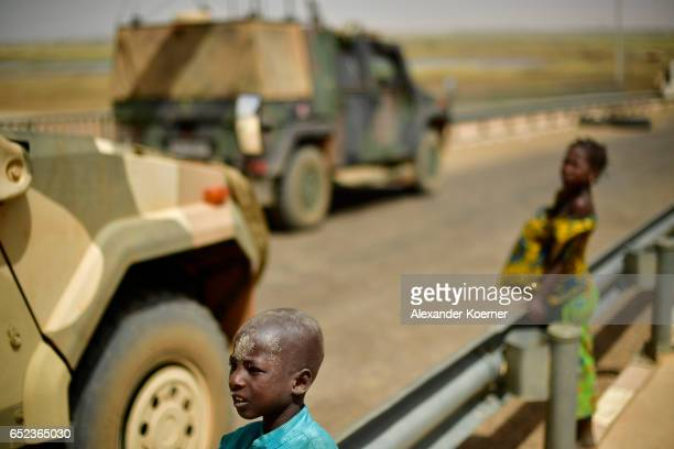 Small boy and his sister watche soldiers of the Bundeswehr, the German Armed Forces, on the bridge of the river Niger after leaving a weekly cattle...