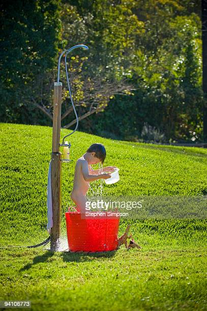 small boy bathes in backyard shower