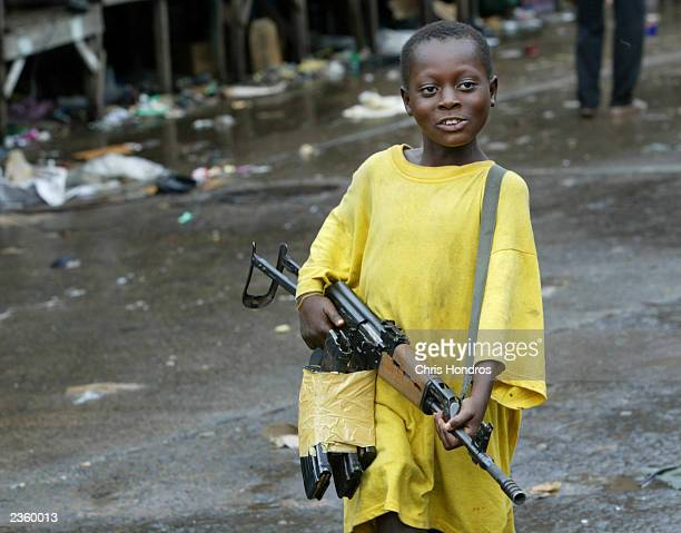 A small boy brandishes an assault rifle near the front lines August 3 2003 in Monrovia Liberia Very small children often hang around the fronts...