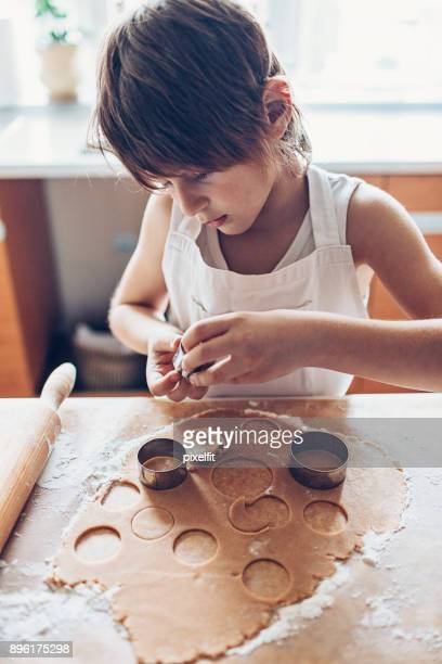 Small boy cutting dough for cookies