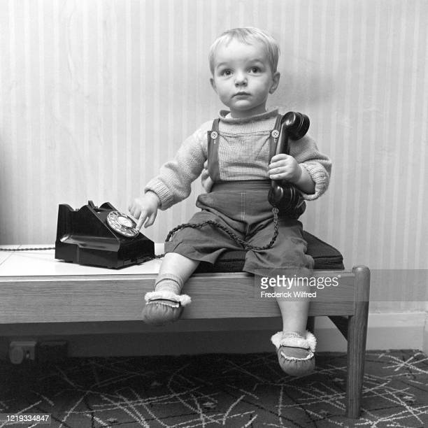 A small boy dialing corded telephone London 1963