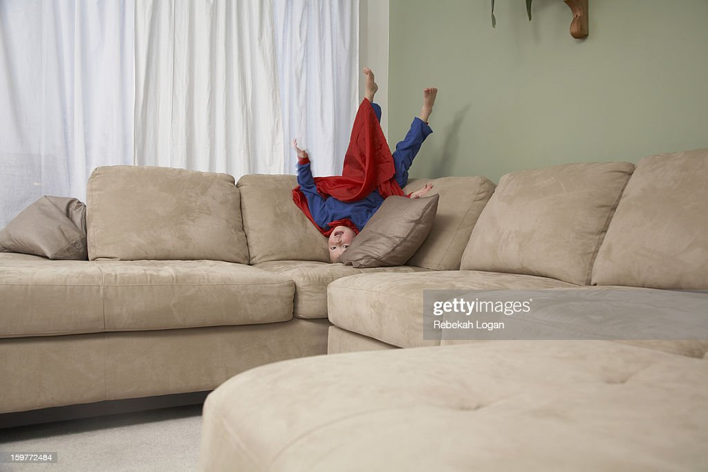 Small boy dressed as superhero jumping on couch. : Stock Photo