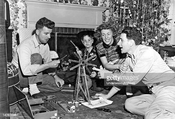 A small boy dressed in a cowboy outfit watches as his parents and friend play with the erector set that he got for Christmas Millbrae California 1950s