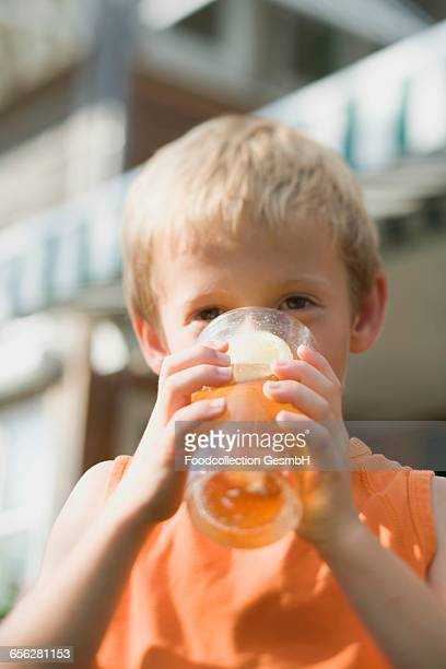 Small boy drinking a glass of iced tea