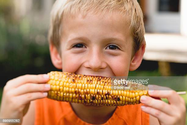 small boy eating grilled corn on the cob - indian corn stock photos and pictures