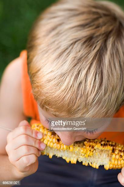 Small boy eating grilled corn on the cob