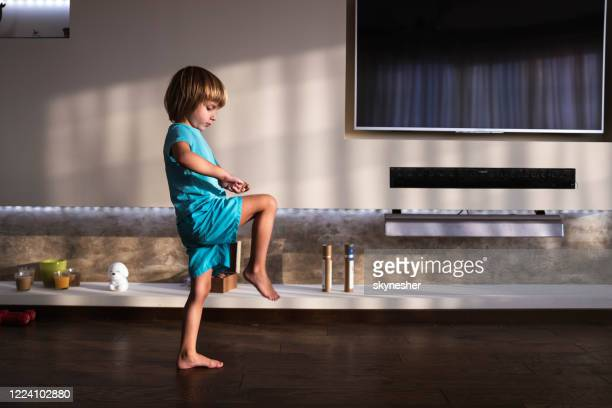 small boy exercising balance in the living room. - standing on one leg stock pictures, royalty-free photos & images