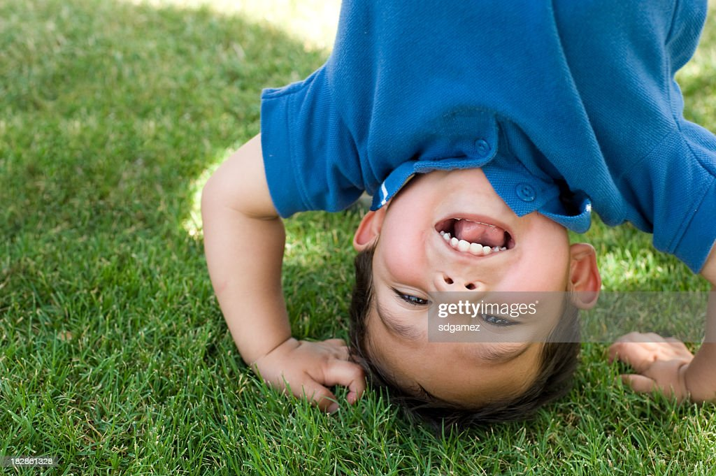 Small boy happily doing a handstand  : Stock Photo