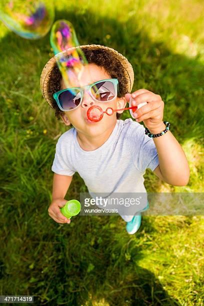 Small boy having fun blowing bubbles