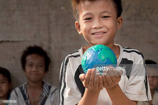 Small boy holding a globe of the world in his hand