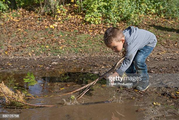 small boy holding branch splashing puddle fun - spaß stock pictures, royalty-free photos & images