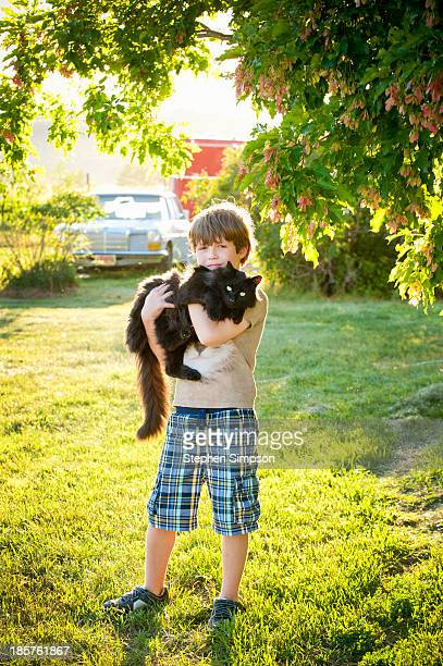 small boy holding large cat, afternoon light
