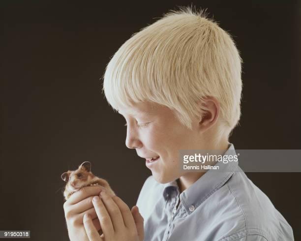 Small boy holding pet gerbil
