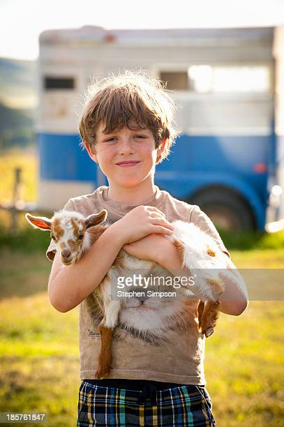 small boy holding small [baby] goat