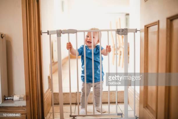 small boy holds on to safety gate - misure di sicurezza foto e immagini stock