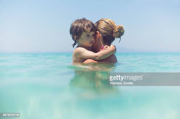 Small boy hugging his mother in the sea