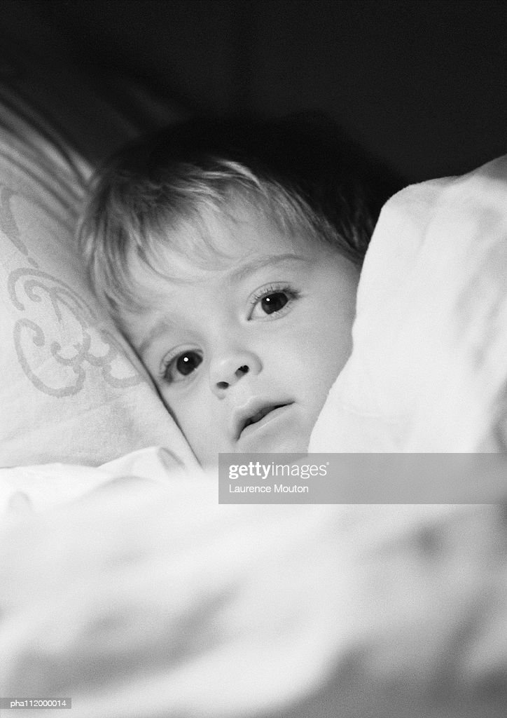 Small boy in bed under blanket, close-up, b&w : Stockfoto