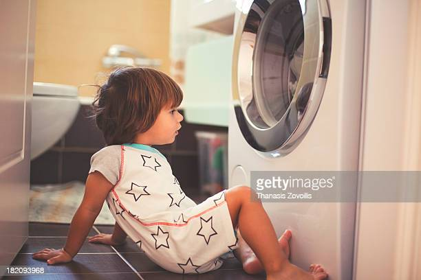Small boy in front of washing machine