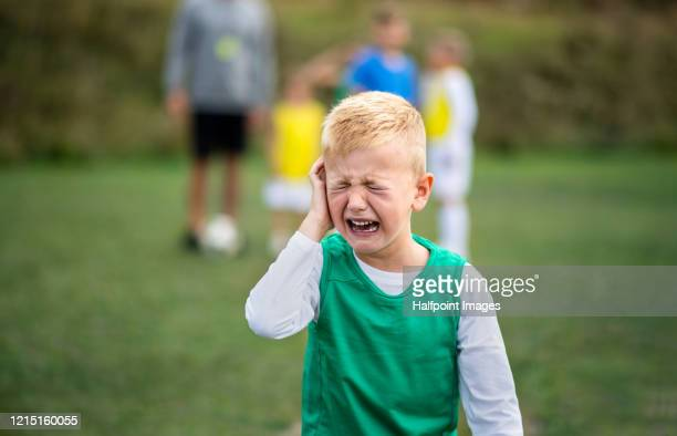 small boy in pain crying outdoors on football pitch. - head coach stockfoto's en -beelden