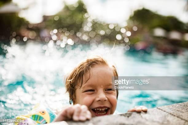 kleiner junge im pool - schwimmen stock-fotos und bilder