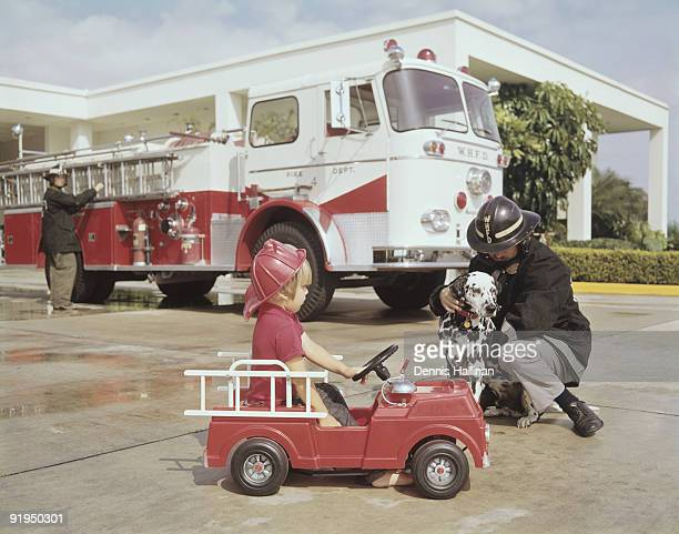 Small boy in toy fire engine and Dalmatian dog at fire station with fireman