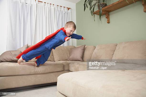 Small boy jumping on couch in costume.