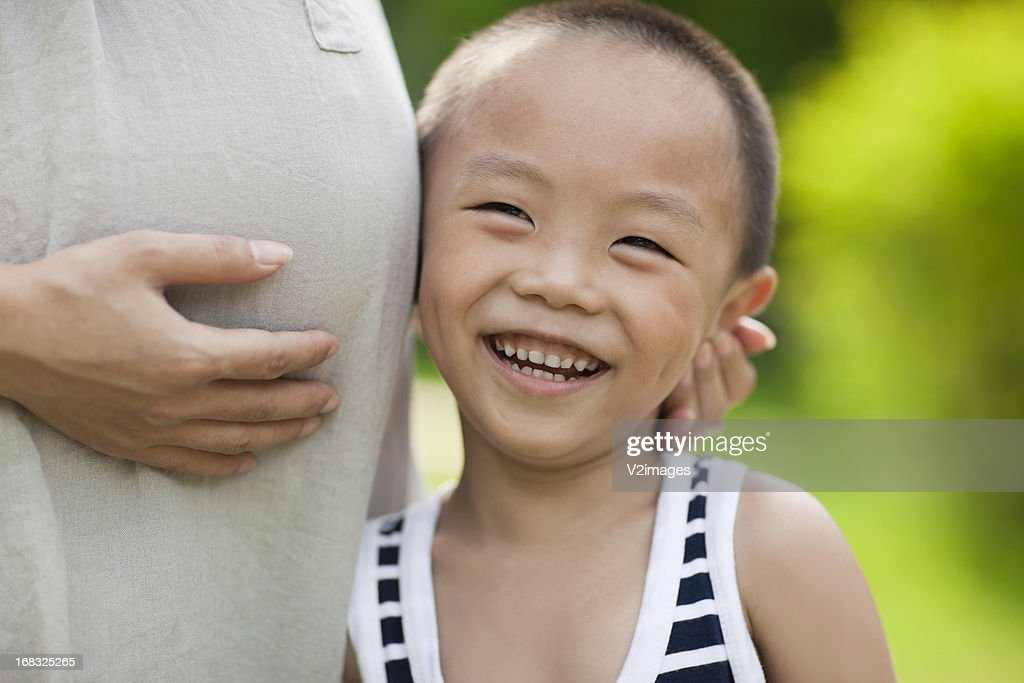 Small boy listening to mother's pregnant tummy : Stock Photo