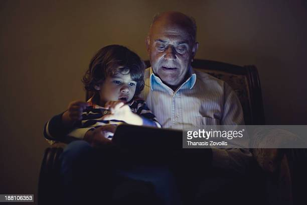 Small boy looking a tablet with his grandfather