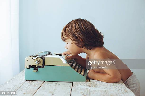 Small boy looking an old typewriter