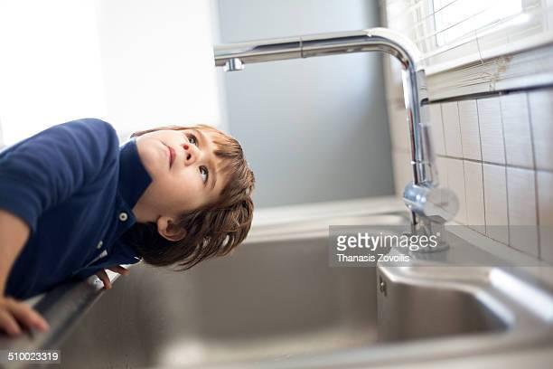 Small boy looking at faucet