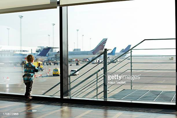 small boy looking out of airport window - only boys stock pictures, royalty-free photos & images