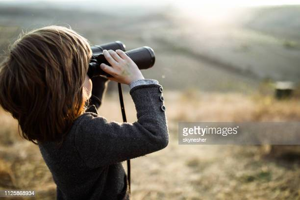 small boy looking through binoculars in nature. - binoculars stock pictures, royalty-free photos & images