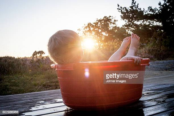 Small boy lying in baby bathtub at sunset