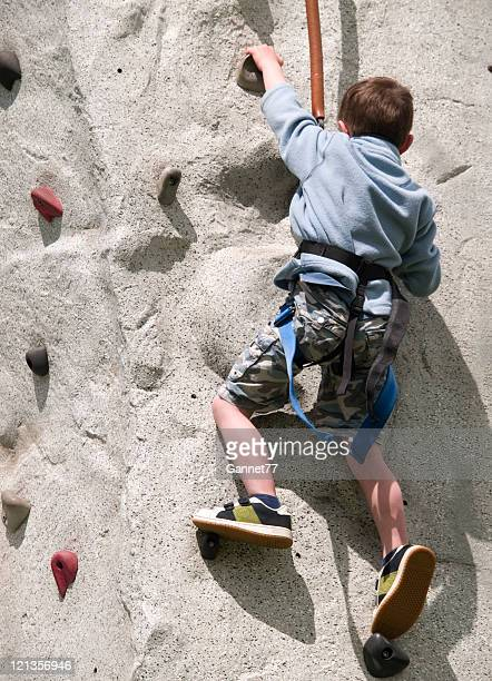 Small boy on climbing wall