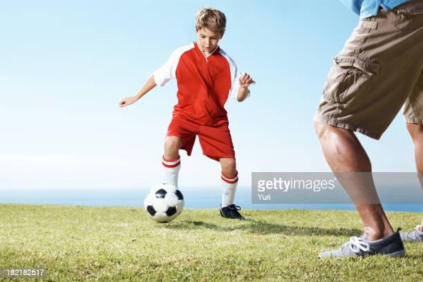 Pequeño niño jugando un partido de fútbol con su padre