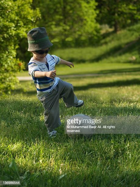 Small boy playing football