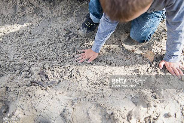 small boy playing in sandbox playground - dreiviertelansicht stock pictures, royalty-free photos & images