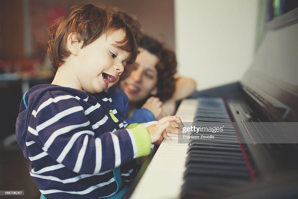 Small boy playing piano : Stock Photo