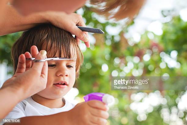 Small boy playing while a woman cutting his hair