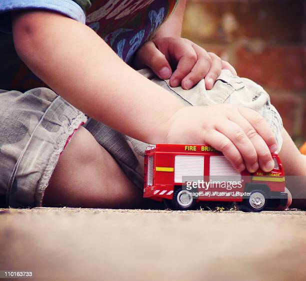 Small boy playing with fire truck