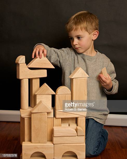 Small boy playing with wooden building blocks