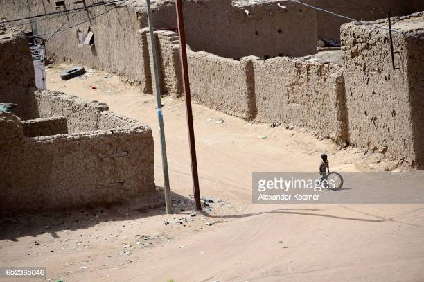 A small boy plays with a rubber wheel in the neighborhood on March 7 2017 in Gao Mali Each week locals and Touareg nomads gather at the market to...