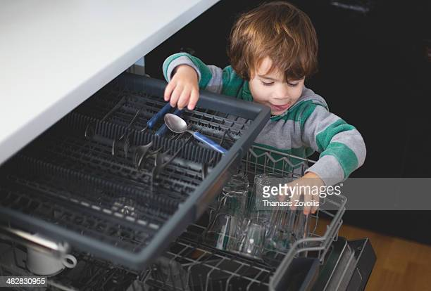Small boy putting a glass in a dishwasher