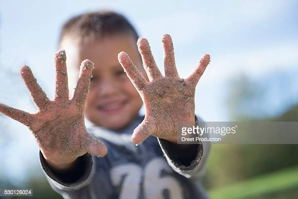 Small boy showing hands covered sand playground