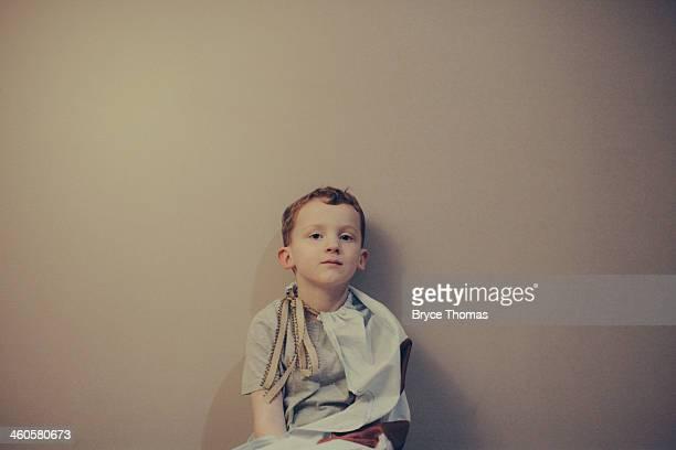 Small boy sits against plain backdrop in tshirt