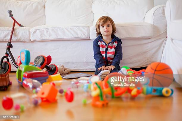 Small boy sitting among his toys